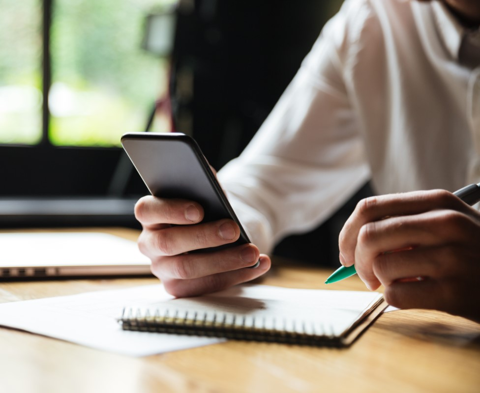 cropped-photo-of-young-man-in-white-shirt-holding-smartphone-while-resting-after-paperwork